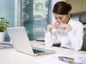 ThinkstockPhotos-Woman looking frustrated in front of computer