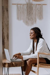 photo of a black woman smiling at her computer